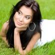 Beautiful young brunette girl on a lawn - Photo
