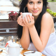 Young woman drinking tea in a caffe outdoors — Stock Photo