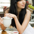 Beautiful woman drinking tea in a cafe — Stock Photo