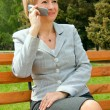 Middle-aged businesswoman in a park - Stock Photo