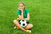 Beautiful young woman with a ball sitting outdoors — Stock Photo