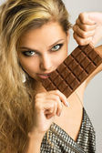 Close-up studio portrait of a beautiful young woman eating choco — Stock Photo