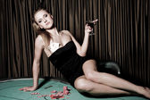 Sexy young girl with glass of wine in casino — Stock Photo