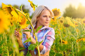 Attractive young blonde girl in sunflowers — Stock Photo