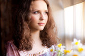 Beautiful young woman looking through a window — Stock Photo