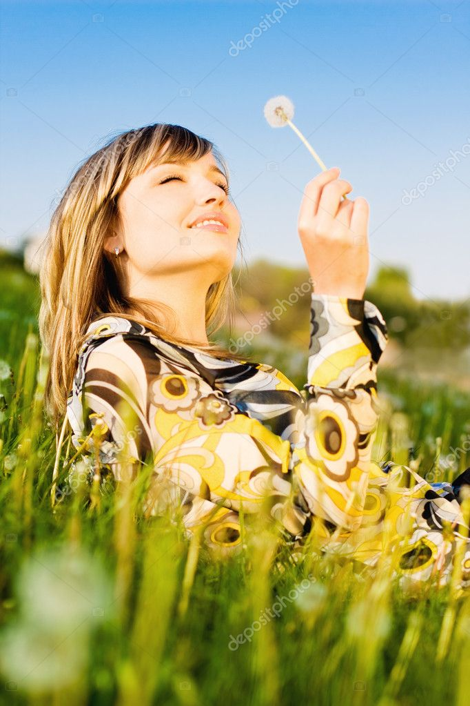Attractive young girl relaxing on a meadow, holding dandelion flower in her hand — Stock Photo #11895622