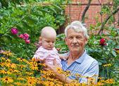 Dziadek z małym wnukiem w ogrodzie kwiatowych — Zdjęcie stockowe