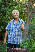 Elderly man with a barbecue — Stock Photo