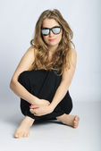 Beautiful girl in black long long gown bespectacled — Stock Photo