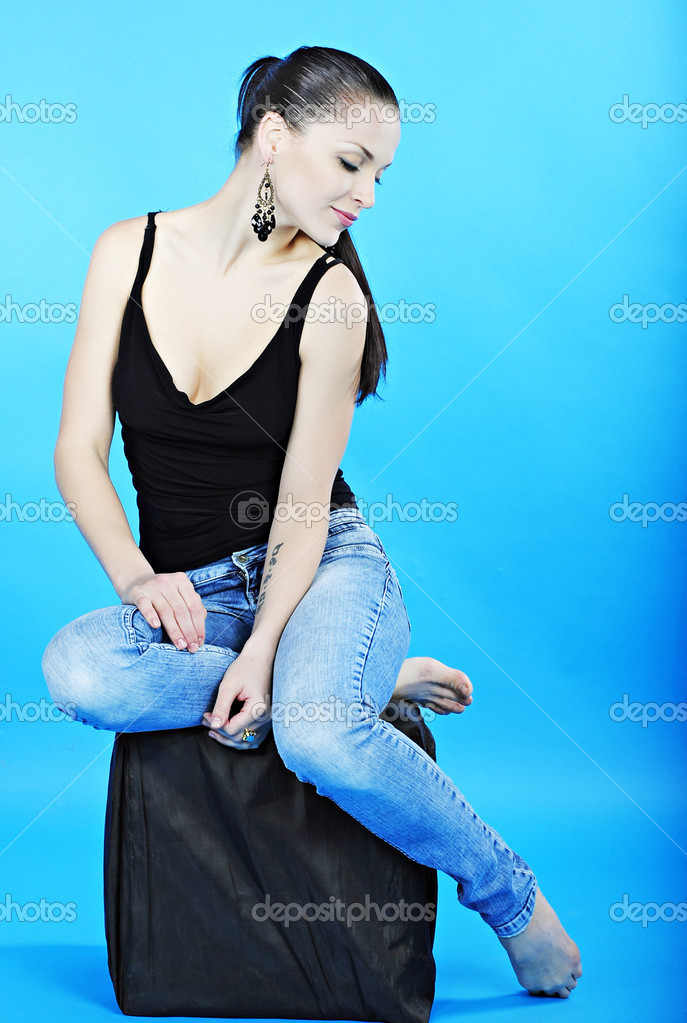 Beautiful graceful girl brunette with long hair on turn blue background in blue jeans — Stock Photo #10830443