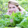 Beautiful girl in wood amongst green sheet — Stock Photo #11303670