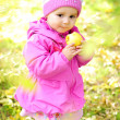 The little girl on a green glade with an apple - Stock Photo