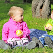 Royalty-Free Stock Photo: Two small children sit on a green clearing eat apples