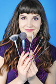 Beautiful girl visagiste with tassel for make-up with long hair — Stock Photo