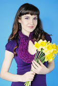 Beautiful girl with long hair with yellow narcissus — Stock Photo