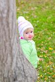 Liten vacker flicka i grön färg på gröna glade av höstens peer — Stockfoto