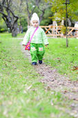 Small beautiful girl in green suit on green glade under yellow s — Stock Photo