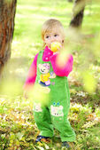 Small beautiful girl on green herb by autumn — Stock Photo