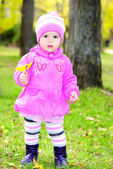 The little girl walks on a green glade — Zdjęcie stockowe