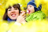 Le petit garçon beau parmi jaune automne feuilles avec maman — Photo