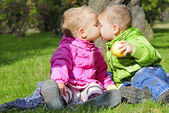Two small children sit on a green clearing eat apples — Stock Photo