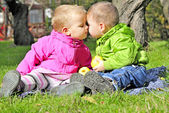 Small children kiss on a green clearing in the autumn — Stock Photo