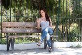 Una donna che riposa su una panchina del parco — Foto Stock