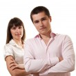Portrait of a cheerful business couple standing together with folded arms on white background — Stock Photo