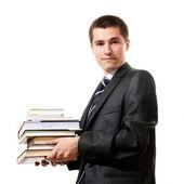 Beau jeune homme d'affaires détenant la pile de livres, isolé — Photo