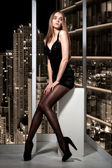 Beautiful woman sitting on window and looking on night city — Stock Photo