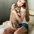 Young woman with little dog sitting on bed — Stock Photo