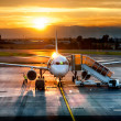 Stock Photo: Airplane near the terminal in an airport at the sunset