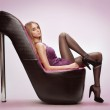 Beautiful young woman sitting on a trendy shoes — Stock Photo