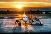 Vliegtuig in de buurt van de terminal in een luchthaven in de zonsondergang — Stockfoto