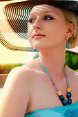 Portrait of pretty cheerful woman wearing white dress and straw hat in sunny warm weather day — Stock Photo