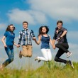 Four teens jumping high in sky — Stock Photo