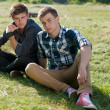 Two young men sitting back to back — Stock Photo