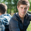 Two young men sitting back to back — Stock Photo #11510621
