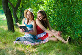 Two happy teenage girls with book outdoors — Stock Photo