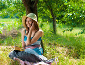 Happy teenage girl with book and mobile phone outdoors — Foto Stock