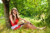 Glücklich teenager-mädchen mit buch und handy im freien — Stockfoto