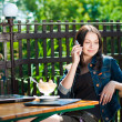 Young happy woman sitting in terrace cafe with laptop — Stok fotoğraf