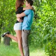 Young happy couple embracing in green park — Stock Photo