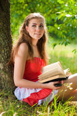 Happy teenage girl with book outdoors — Stock Photo