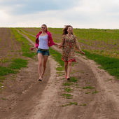 Two happy girls running on country road — Stock Photo