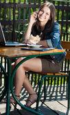 年轻快乐的女人坐在露台咖啡馆与便携式计算机 — 图库照片