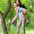 Young happy couple playing in park — Stock Photo