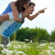 Young happy couple standing on green grass — Stock Photo