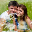 Young happy couple sitting on green grass — Stock Photo