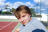 Smart smiling boy at the outdoor tennis court — Stock Photo